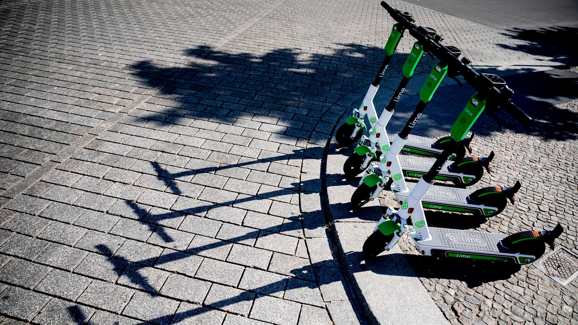 Vier grün-weiße E-Roller auf Kopfsteinpflaster