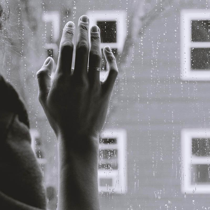 Frau steht am Fenster und schaut hinaus.