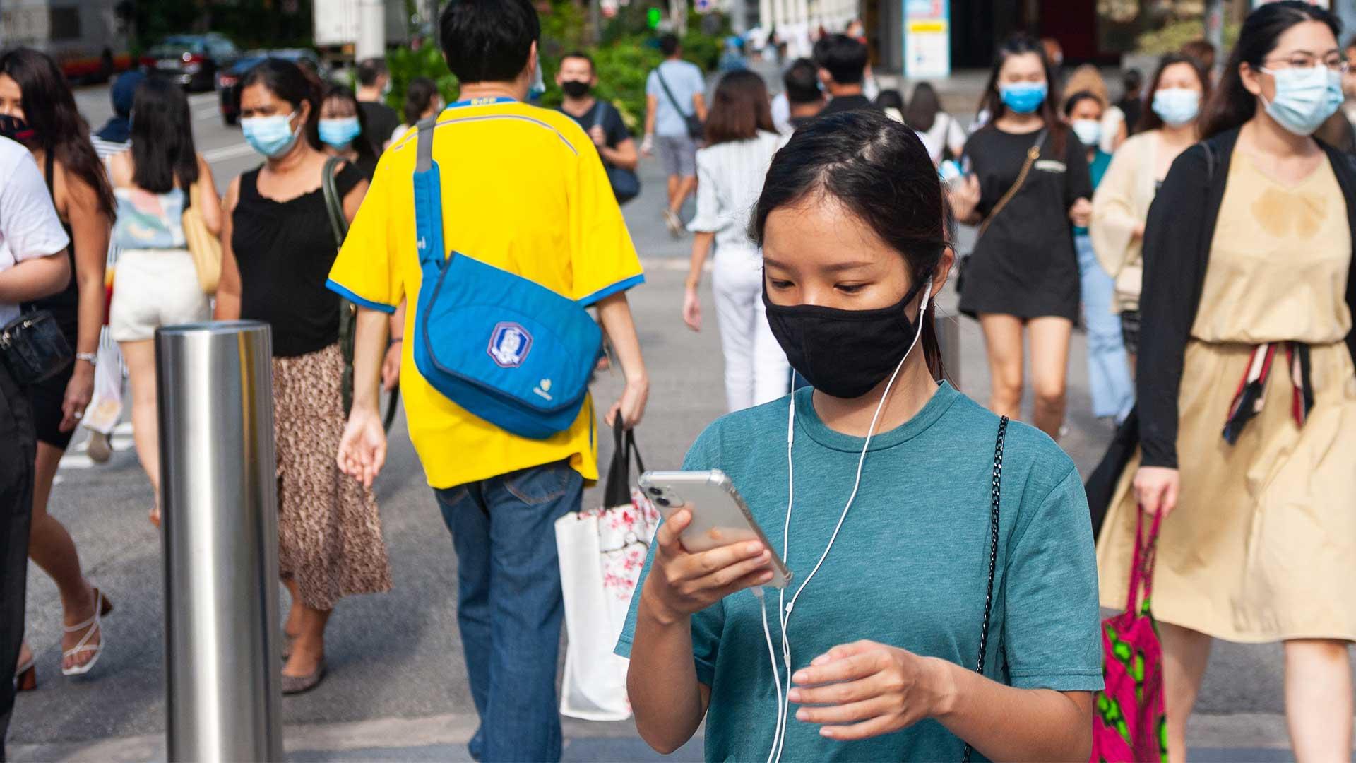 Fußgänger mit Mundschutz gehen die Orchard Road im Stadtzentrum von Singapur entlang. Alle Menschen tragen Masken, im Vordergrund ist eine Frau zu sehen, die auf ihr Handy schaut.