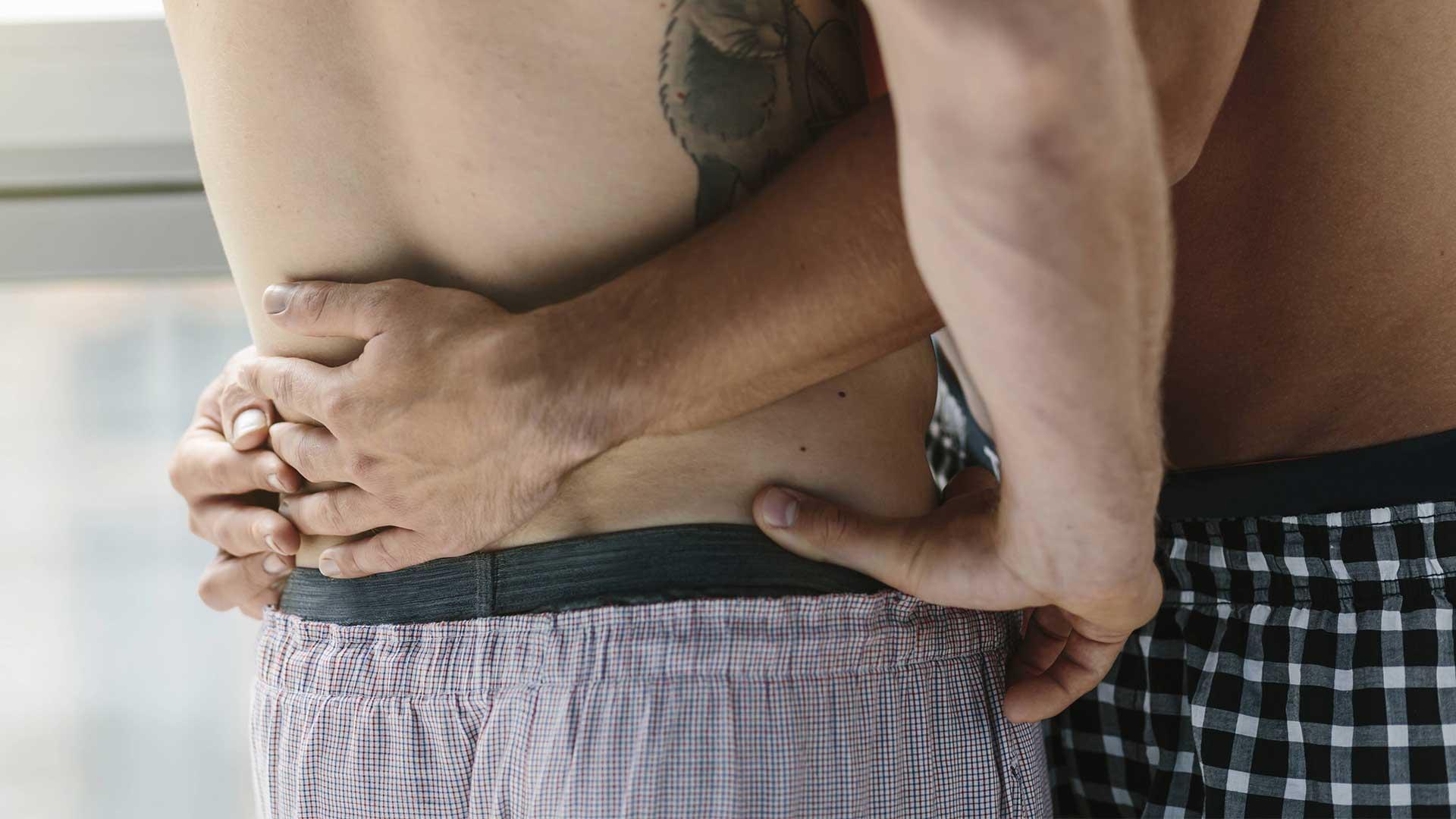 Zärtlicher Körperkontakt zwischen zwei Männern.