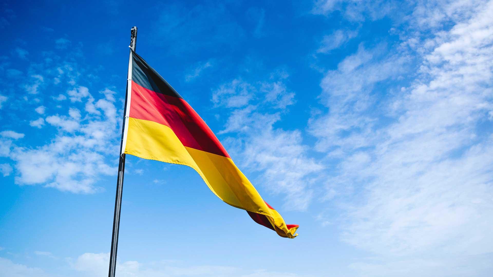Deutsche Flagge vor Wolkenhimmel.