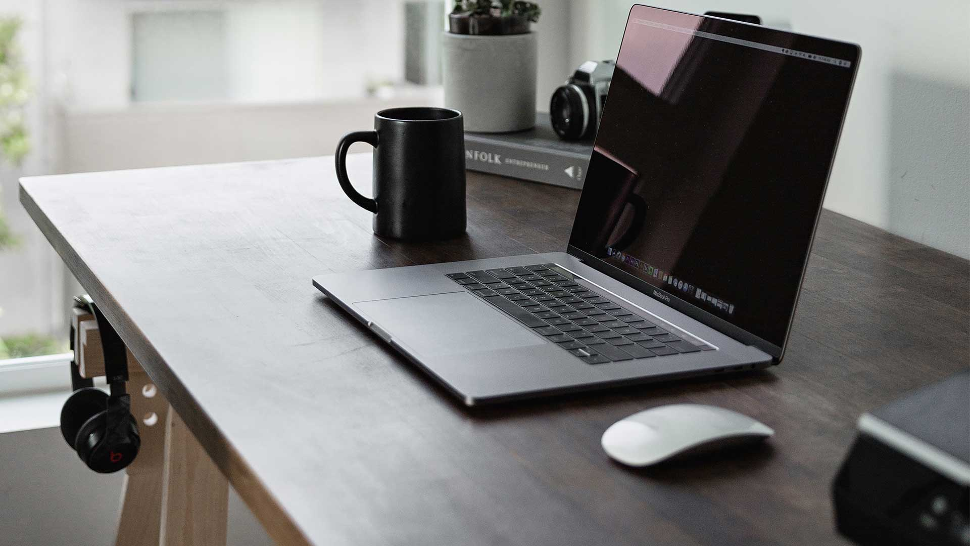 Home Office Schreibtisch am Fenster mit Laptop, Maus, Kaffeetassen und weiteren Büroutensilien. Bild: Dillon Shook/unsplash,