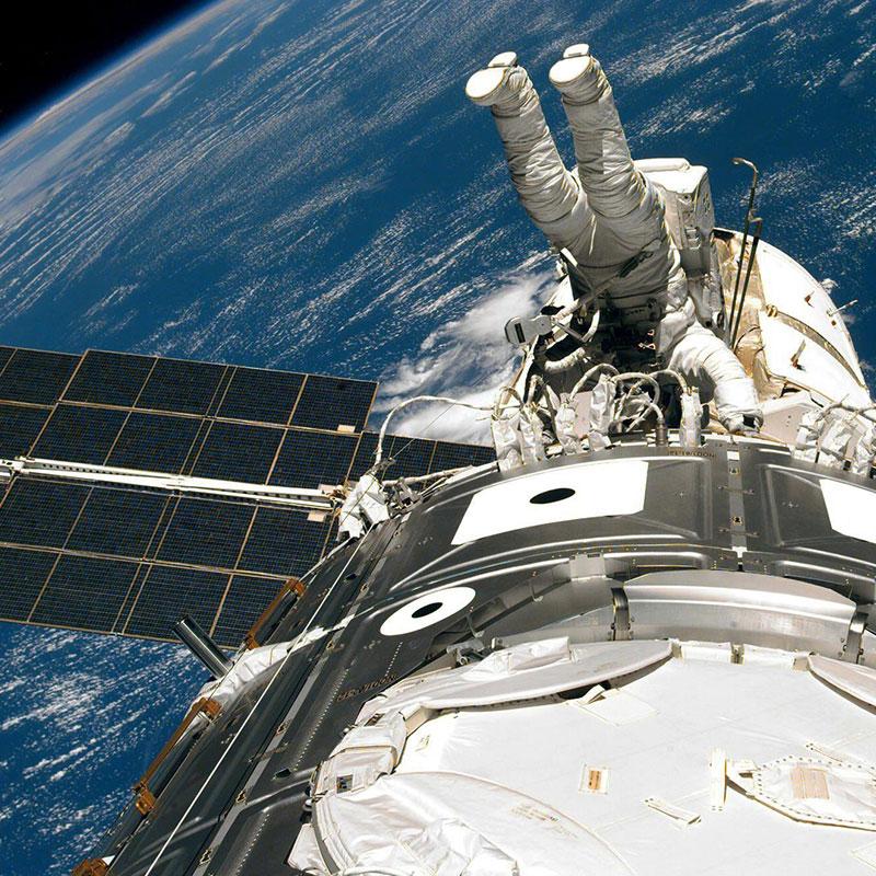 Astronaut arbeitet kopfüber an der Internationalen Raumstation.