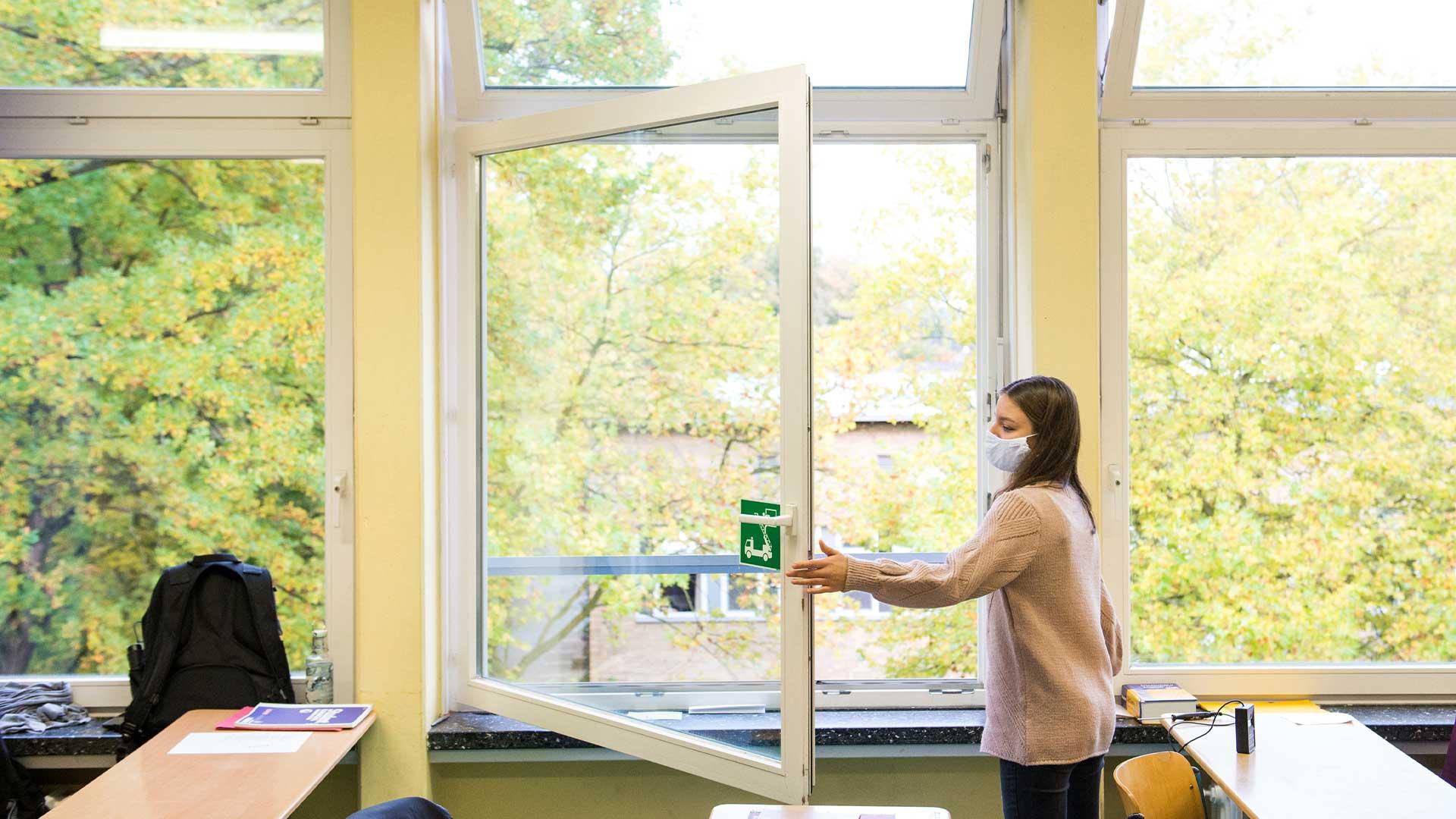Ein Mädchen mit Maske öffnet im Klassenzimmer das Fenster