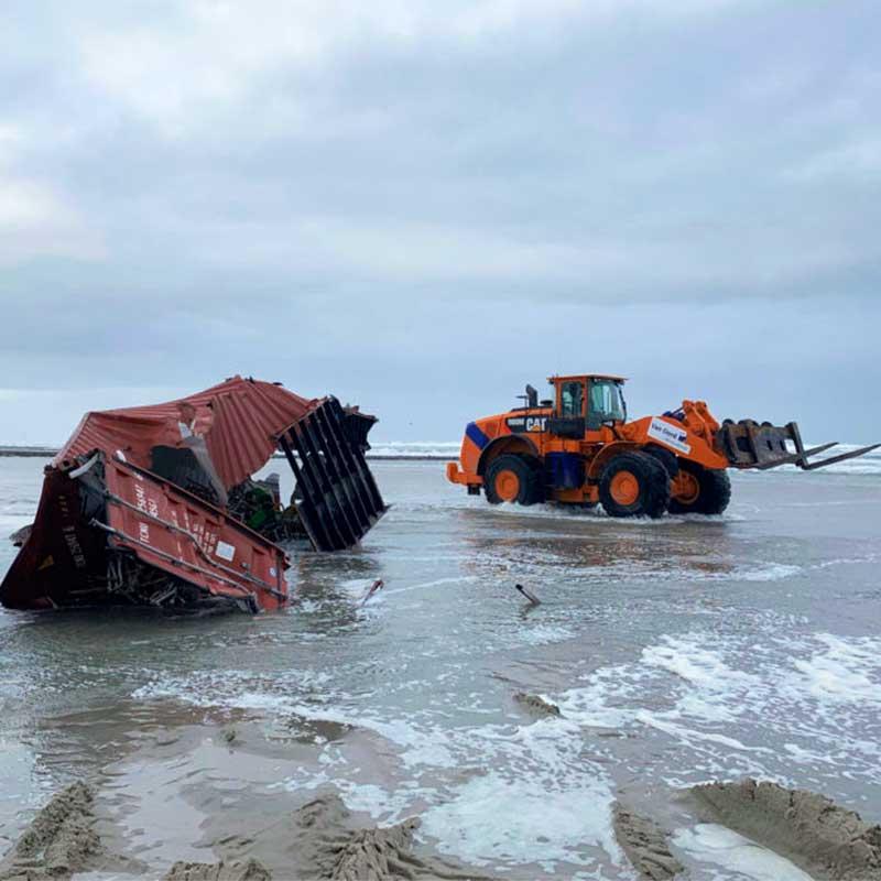 Die Trümmer von Frachtcontainern werden von einem Strand entfernt.