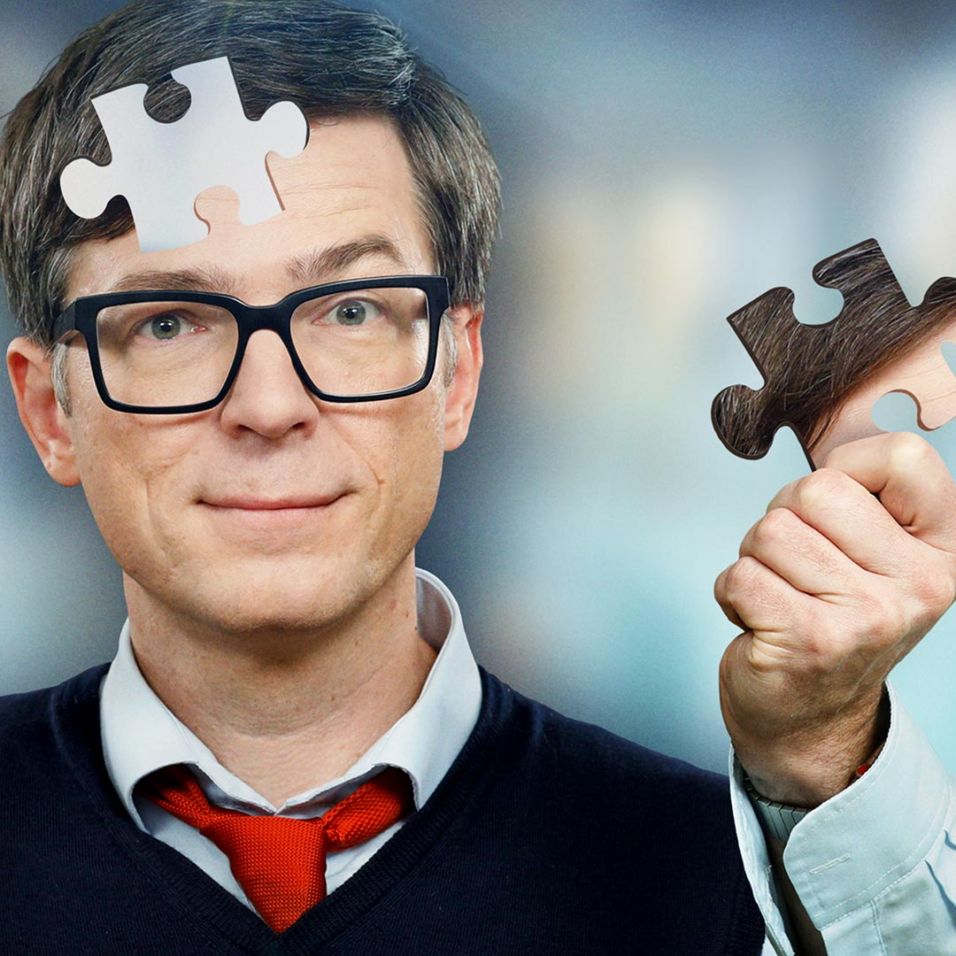 Montage: Ralph Caspers hält Puzzlestück seines Kopfes in der Hand