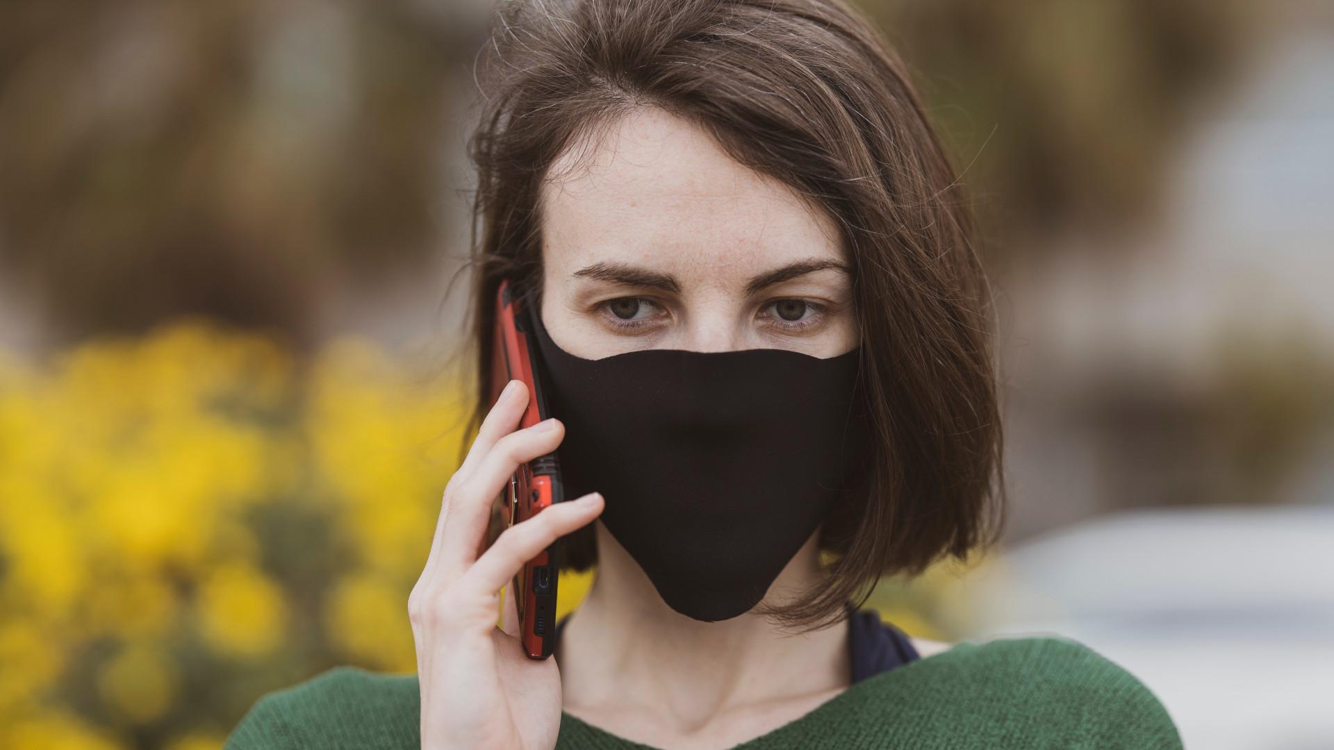 Frau telefoniert mit Maske