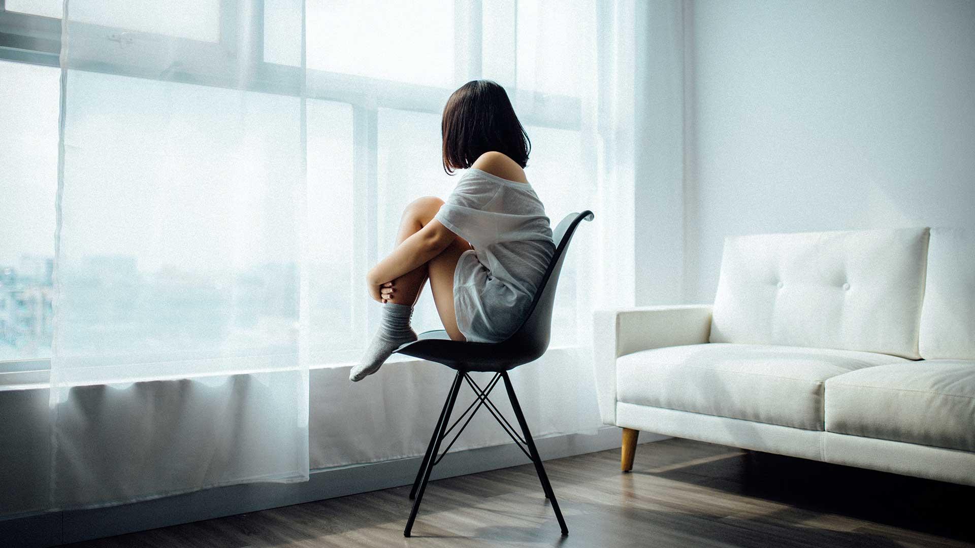 Eine Frau sitzt mit angezogenen Beinen alleine in einem Raum auf einem Stuhl und schaut aus dem Fenster.
