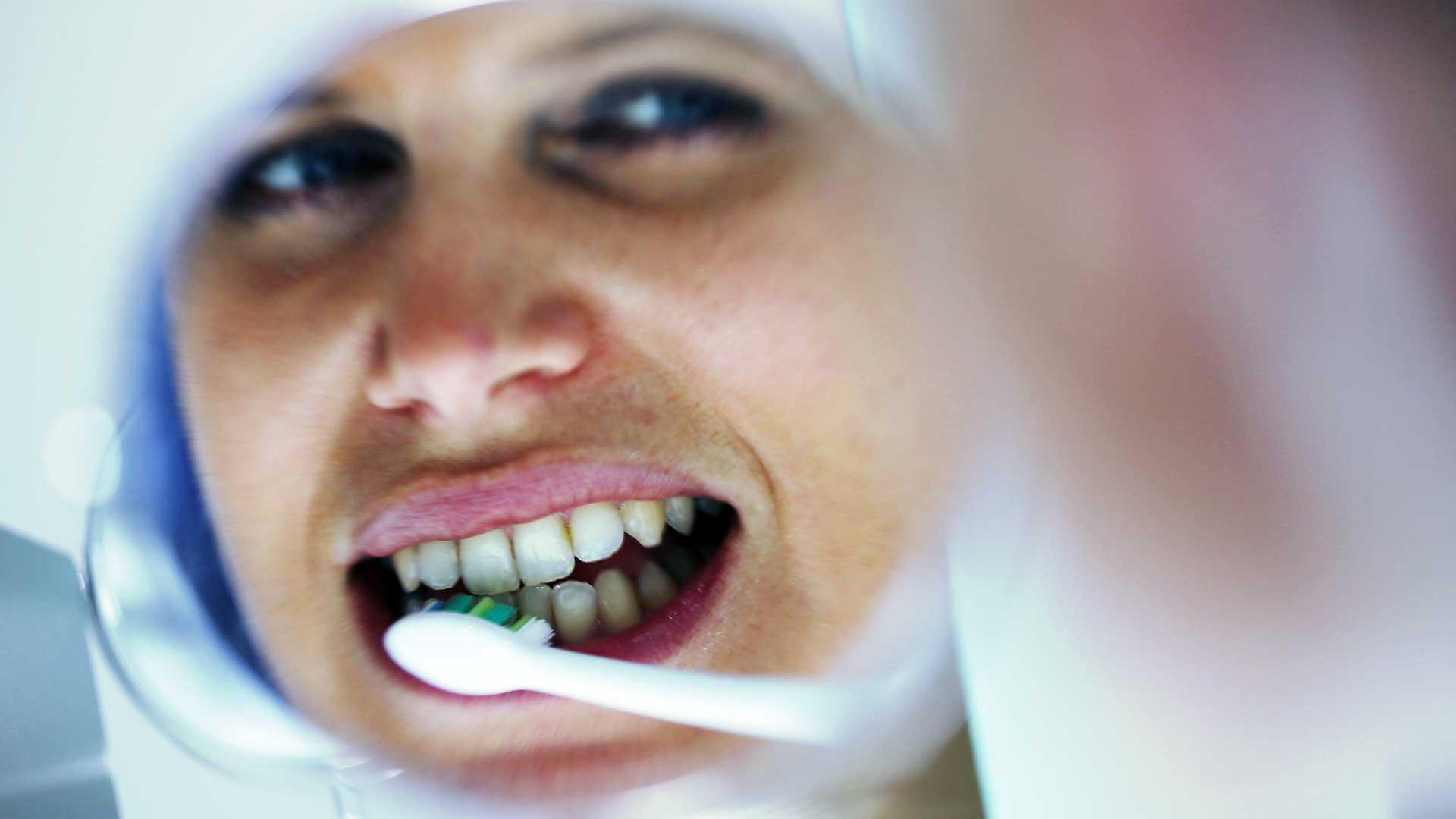 Frau putzt sich vorm Spiegel die Zähne.
