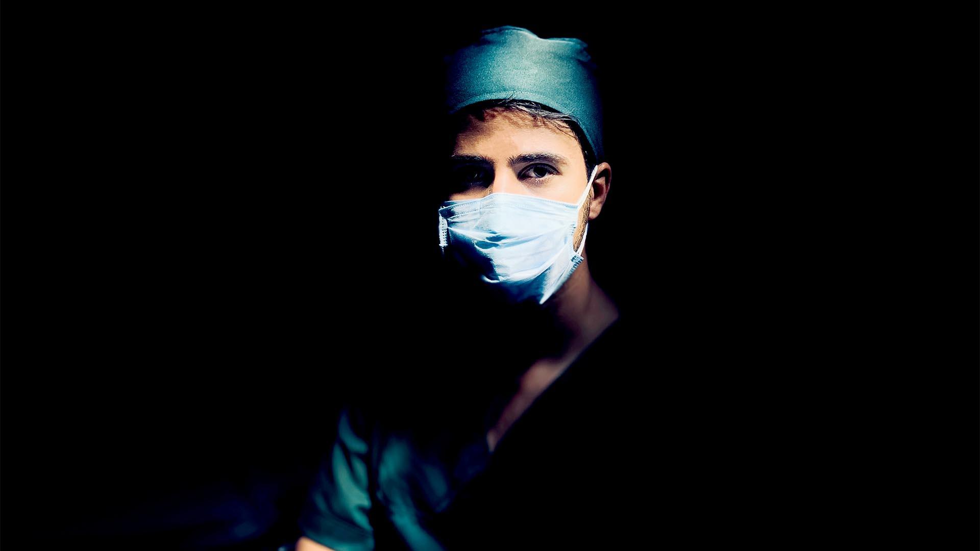 Arzt mit Maske vor dunklem Hintergrund