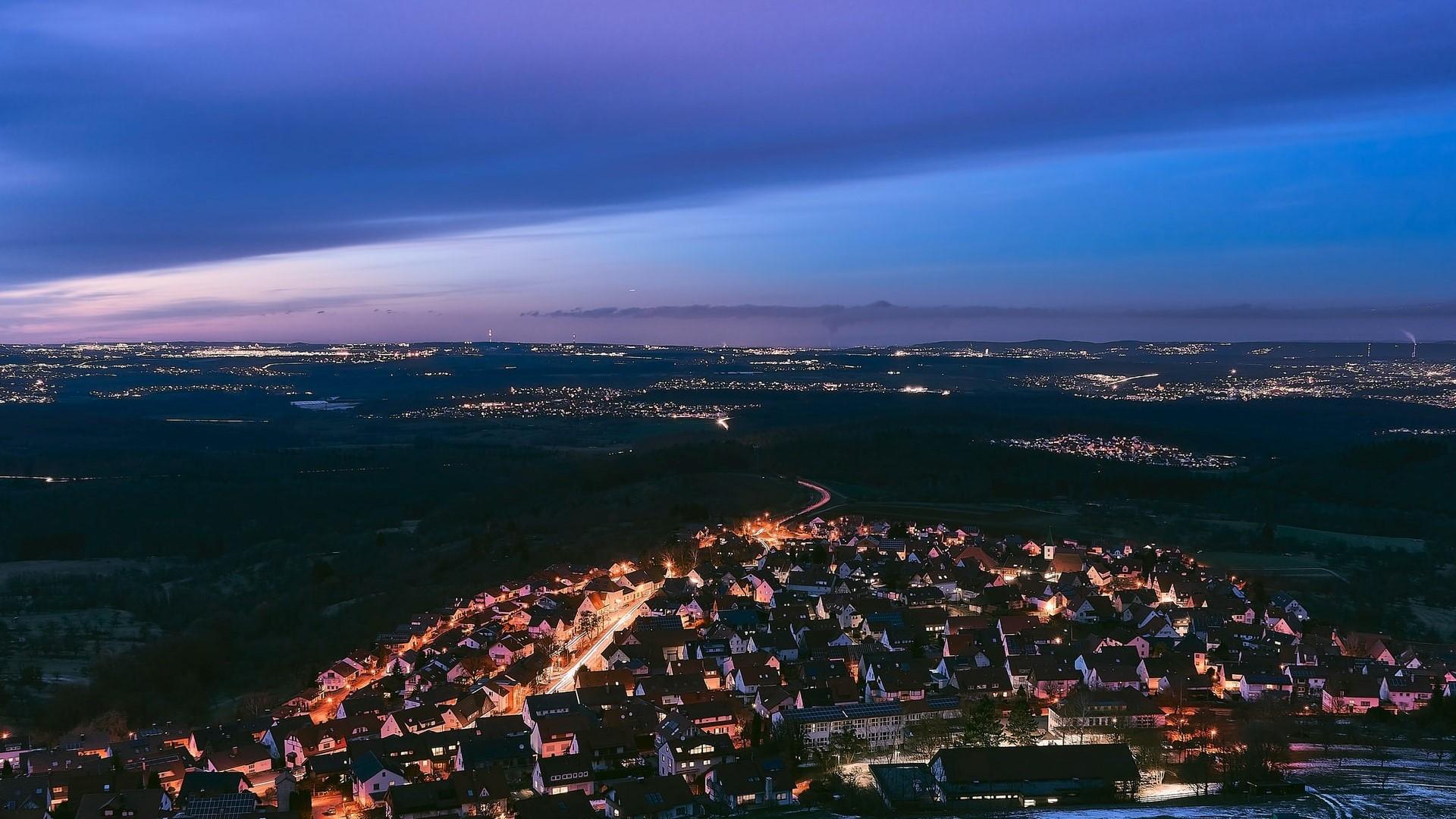 Eine hell erleuchtete Kleinstadt, umgeben von einem verschneiten Feld. In der Ferne sieht man die Lichter weiterer Städte in der Dunkelheit.