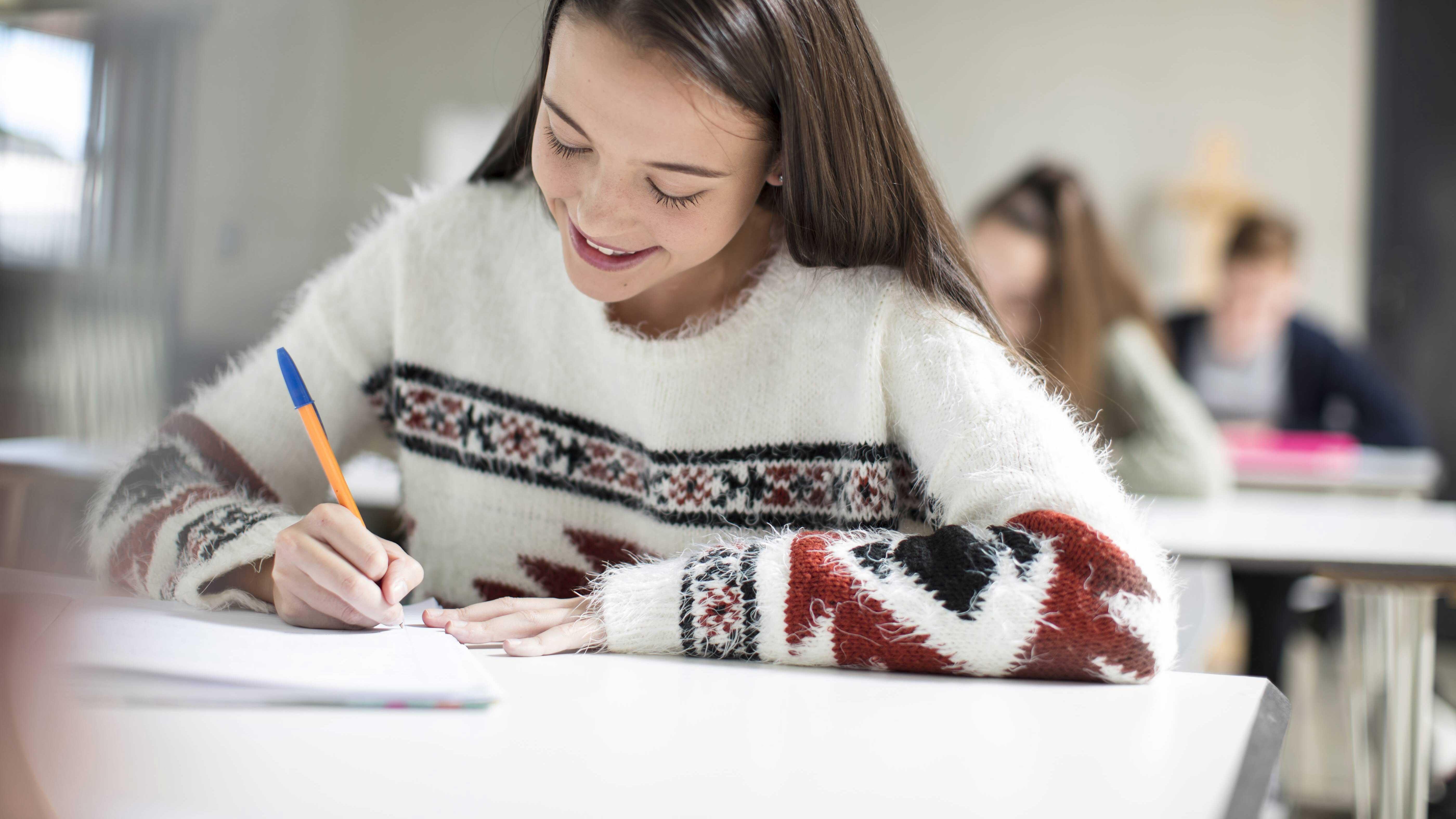 Mädchen sitzt lächelnd an einem Tisch und schreibt mit einem Kugelschreiber