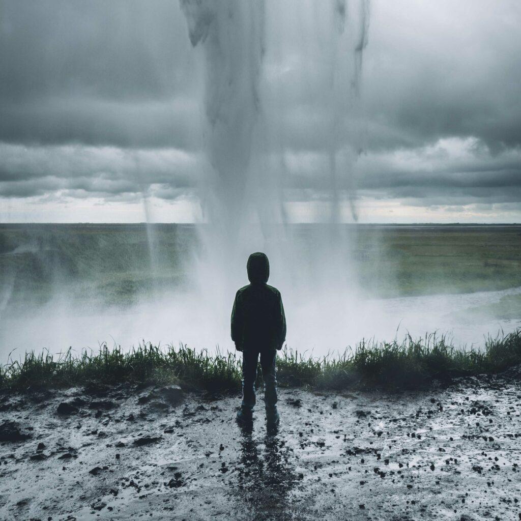 Junge steht mit dem Rücken zur Ansicht im Matsch und es regnet und stürmt