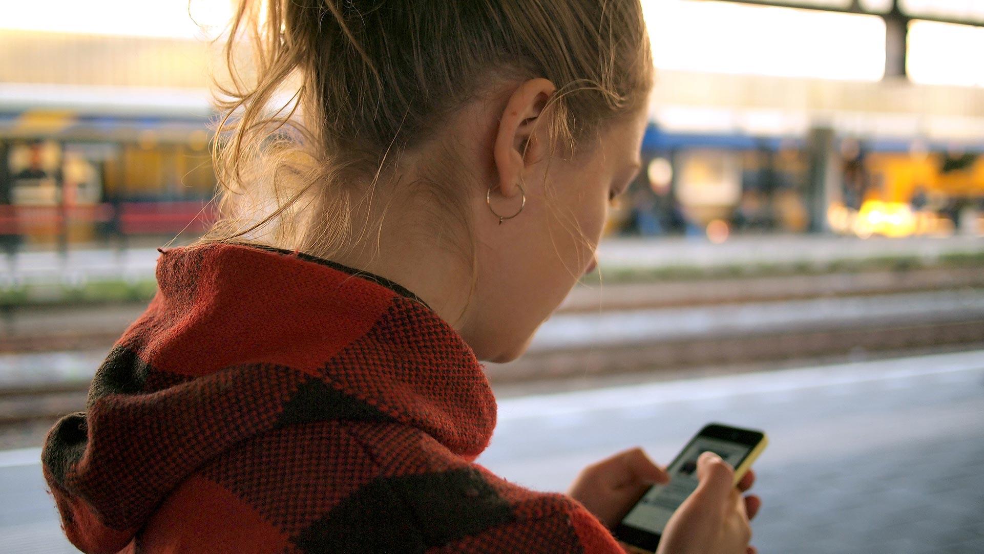 Frau hält Handy am Bahngleis