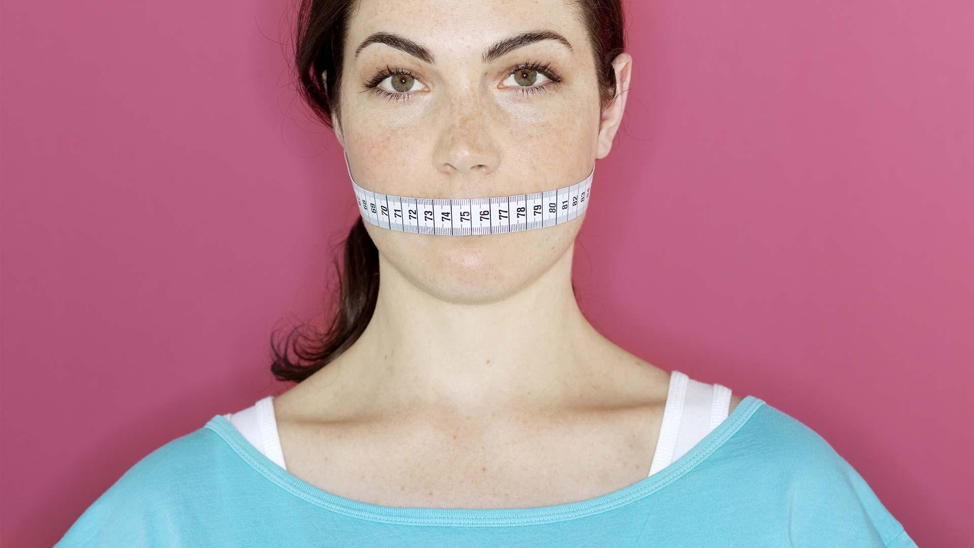 Frau mit Maßband über den Mund