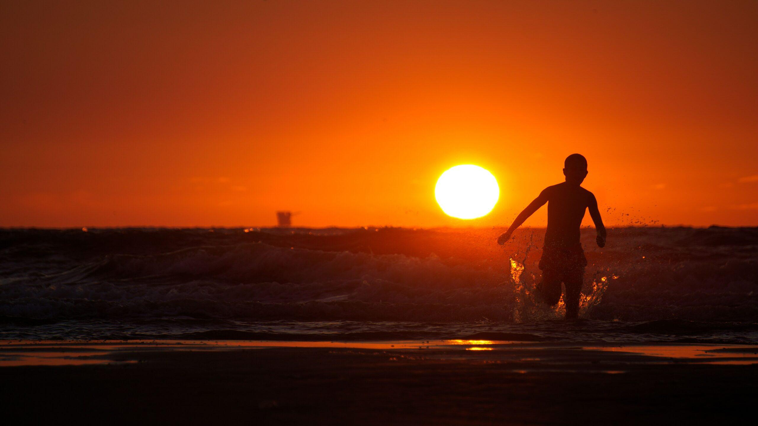 Ein Kind läuft vor einem Sonnenuntergang ins Meer.